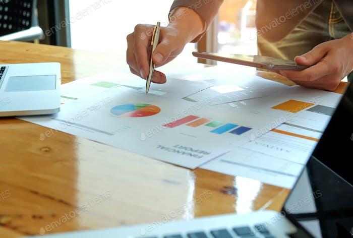 Geschäftsleute analysieren Daten mit Tablet und Grafiken.