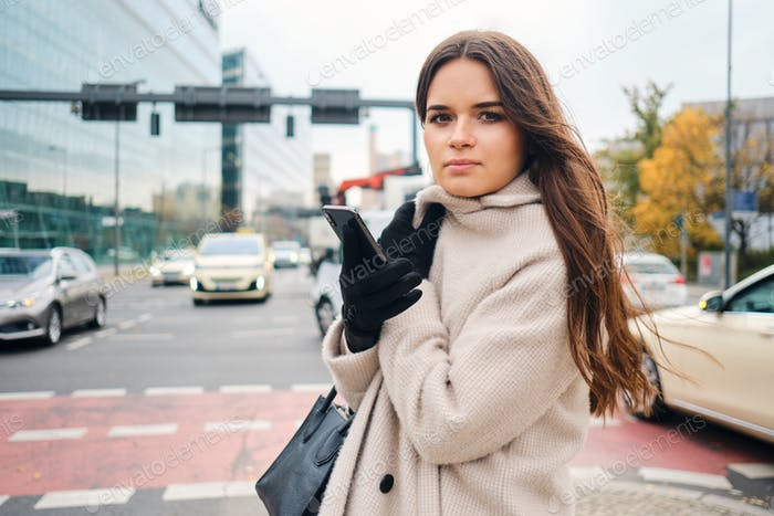 Stylish brunette girl in coat with cellphone intently looking in camera walking around street