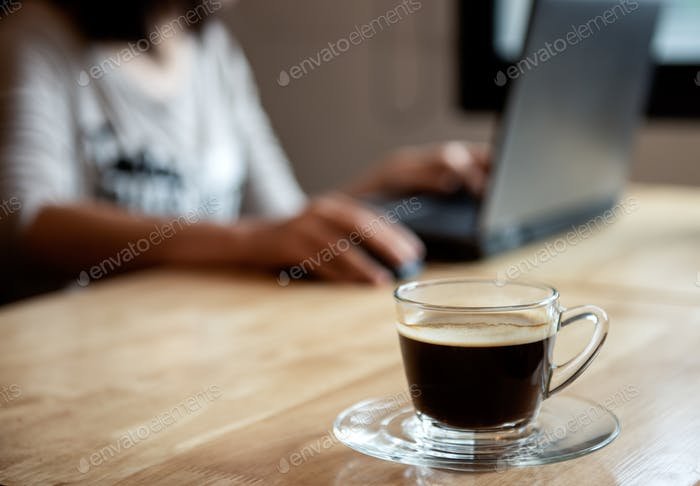 Coffee on wooden table with blurred office girl background.