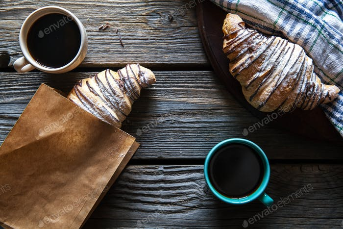 Croissant in a paper bag with a cup of coffee. Breakfast, snack, food