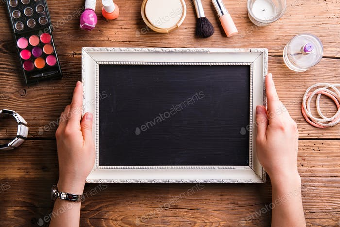Unrecognizable woman holding empty picture frame, various make-u