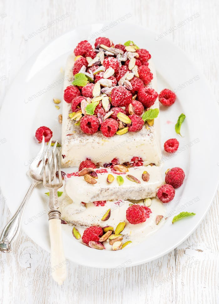 Homemade semifreddo with pistachio, raspberries and mint leaves