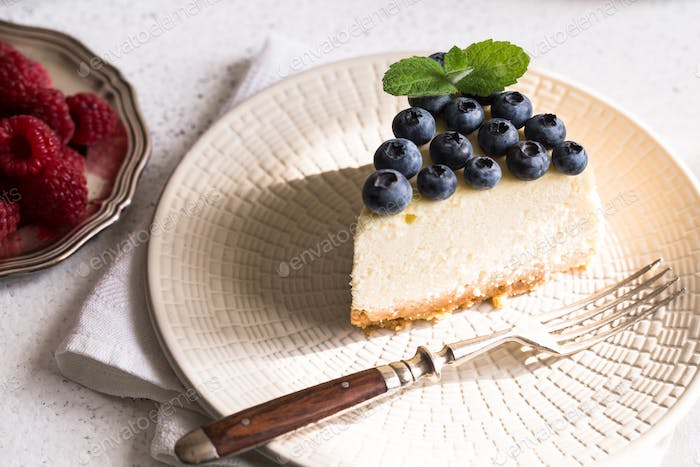 Slice Of Classical New York Cheesecake with blueberries On White Plate