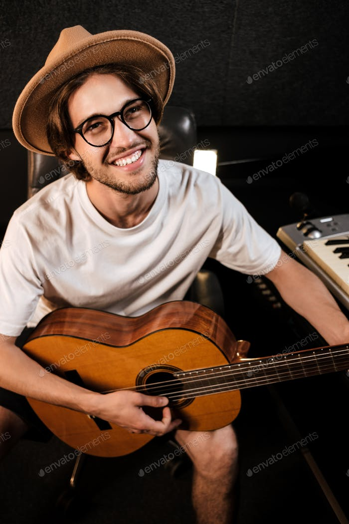 Portrait of attractive cheerful man happily playing on a guitar recording new song in music studio
