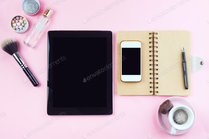 Woman's workplace with coffee, tablet, phone and cosmetics . Top view on pink background, mock