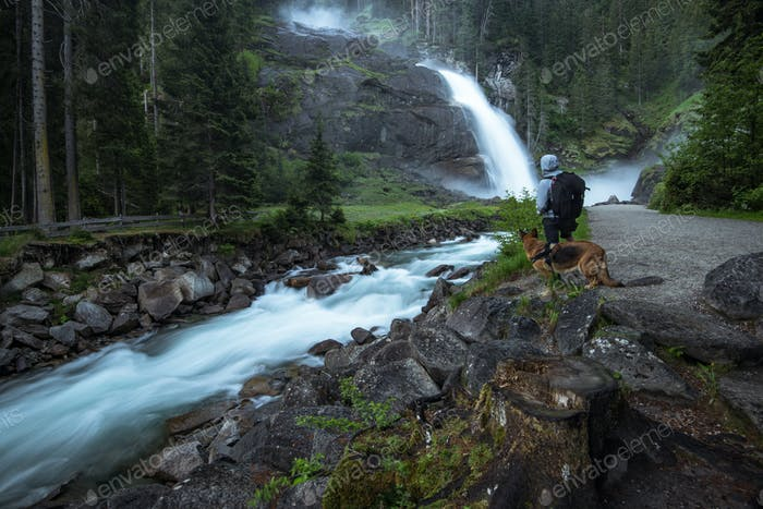 Man and dog watching Krimml Waterfalls in High Tauern National P