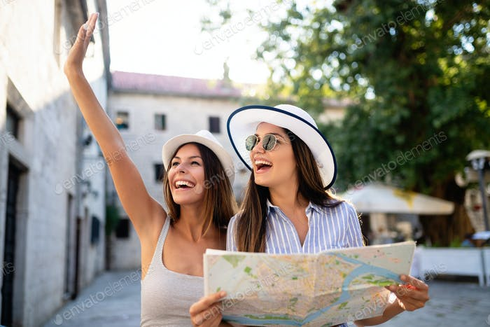 Young happy tourists women sightseeing in city on vacation