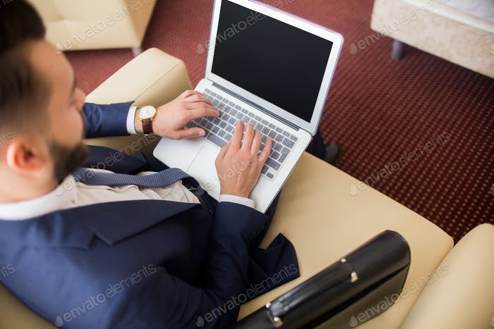 Businessman Working with Laptop in Hotel