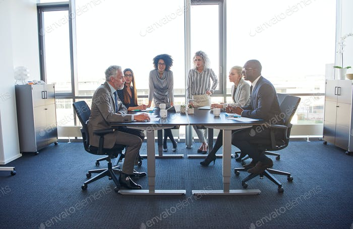 Diverse group of businesspeople meeting together in a modern office