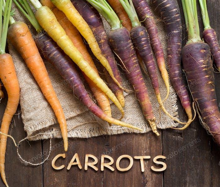 Fresh organic rainbow carrots and word Carrots on wood