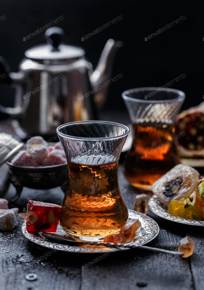 A glowing traditional glass of tea with blurred dark background