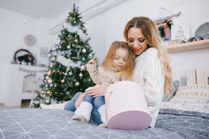 mother and beautiful blonde baby girl opening gifts