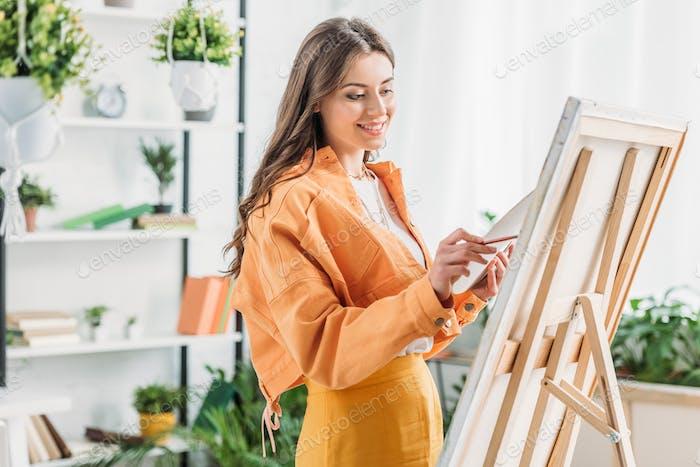 joven artista atractiva sonriendo mientras dibuja sobre lienzo con pincel