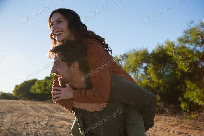 Man giving woman piggyback ride on field