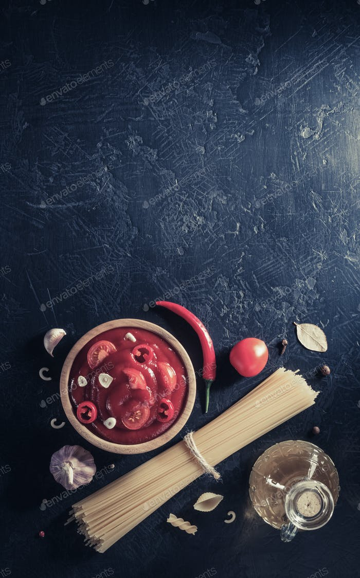 tomato sauce in bowl and pasta on black background