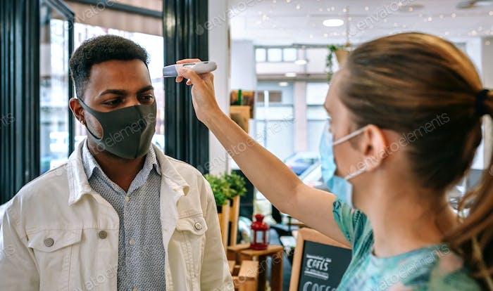 Geschäftsinhaber überprüfen Kunden auf Fieber