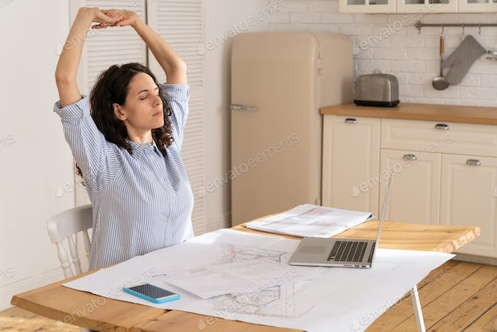 Businesswoman stretch to relieve tension from sedentary work in remote office at home in covid-19