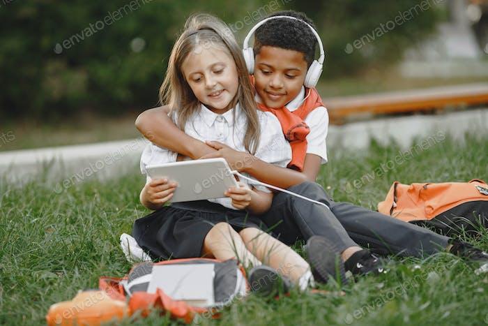 Маленький африканский мальчик учится с кавказской девочкой