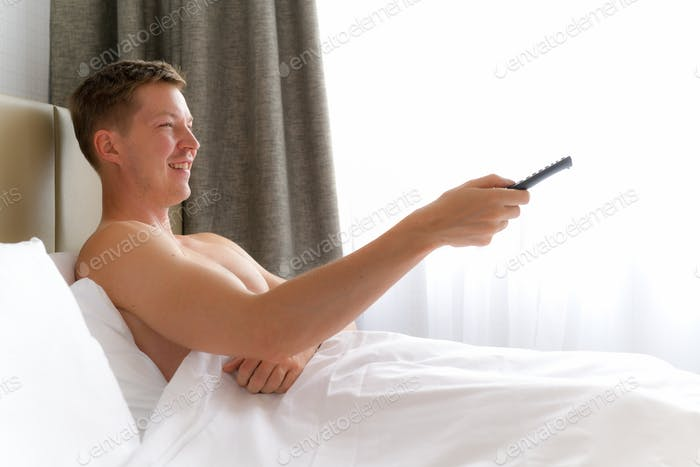Man In Bed Watching Television And Holding Tv Remote