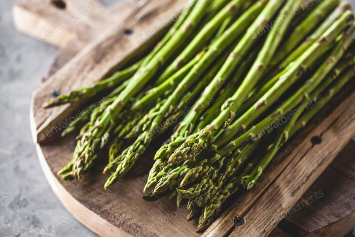 Asparagus on a cutting board. Healthy food, health on a concrete background