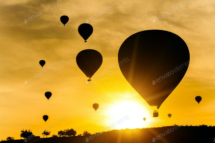 Many balloons at sunset sky background