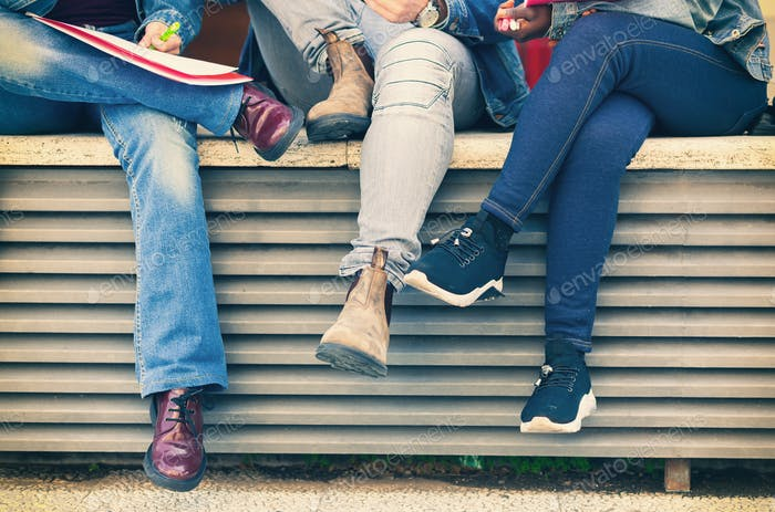 Legs of students sitting on a bench.