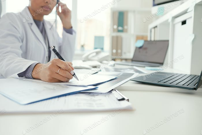 Doctor filling the medical forms