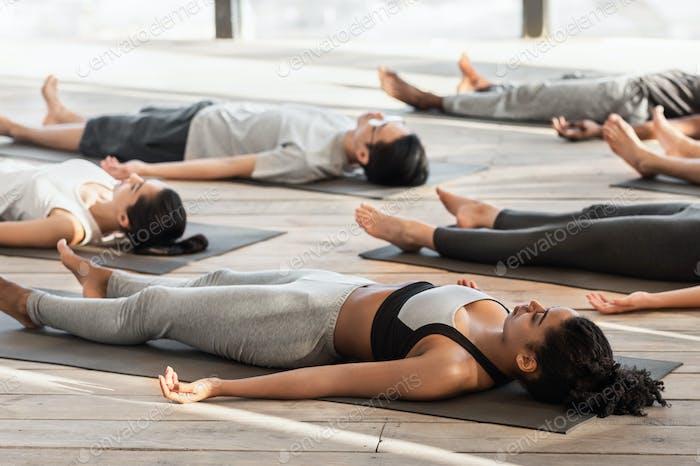 Savasana Pose. Diverse Yoga-Kursmitglieder, die auf dem Boden meditieren, auf Matten liegen