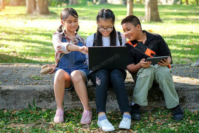 Asian children are playing laptop computer in the park.