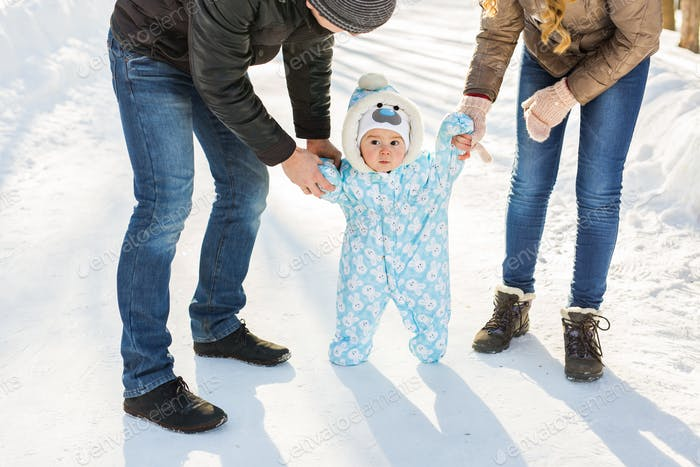 First steps. Little baby learning to walk. Mother and father with toddler boy at the winter park