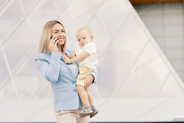 Porträt einer erfolgreichen Geschäftsfrau im blauen Anzug mit Baby