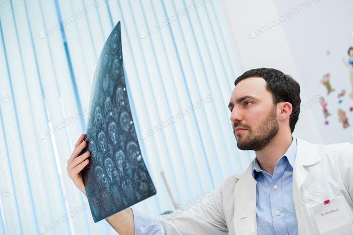 Nahaufnahme Porträt von intellektuellen Mann Gesundheitspersonal mit weißem Labcoat, Blick auf Gehirn Röntgen
