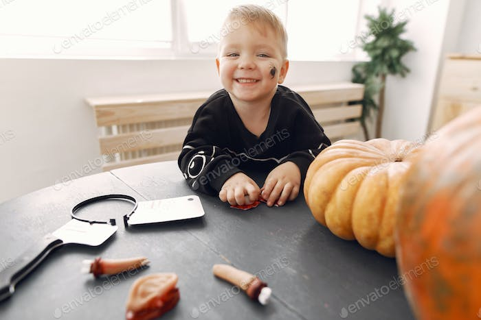 Cute little child with pumpkin at home