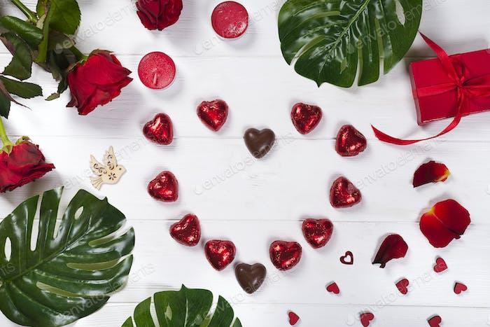 Herz aus Pralinen auf weißem Holzhintergrund