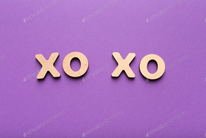 Wooden letters spelling xo-xo on violet background