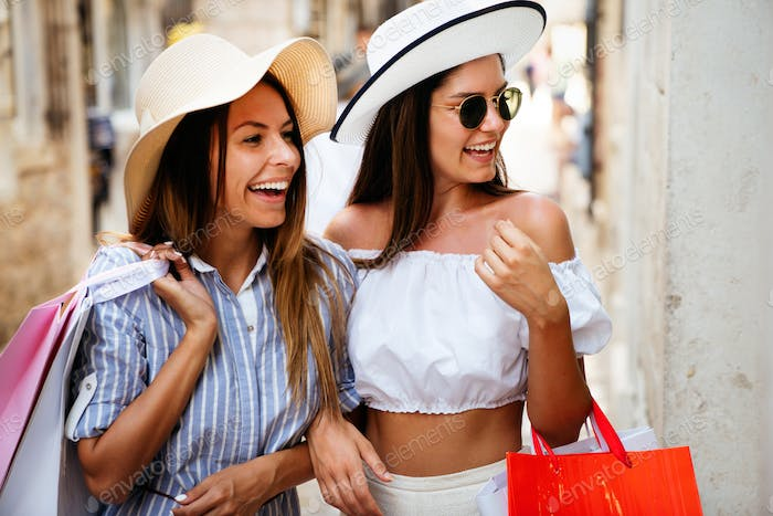 Shopping and tourism concept. Beautiful girls with shopping bag in ctiy