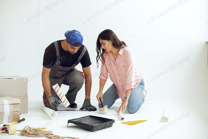 Die junge und niedliche Familie repariert das Zimmer