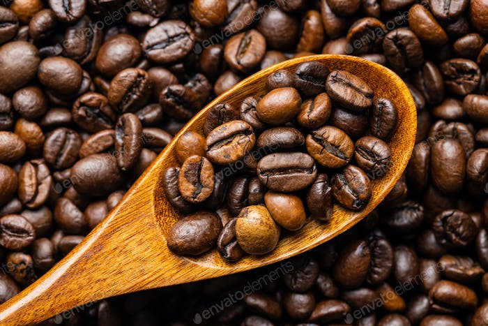 Mixed coffee beans in wooden spoon. Arabica and robusta.