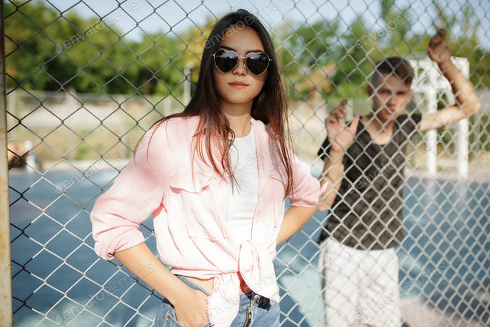 Pretty girl with dark hair in sunglasses near mesh fence and boy on basketball court