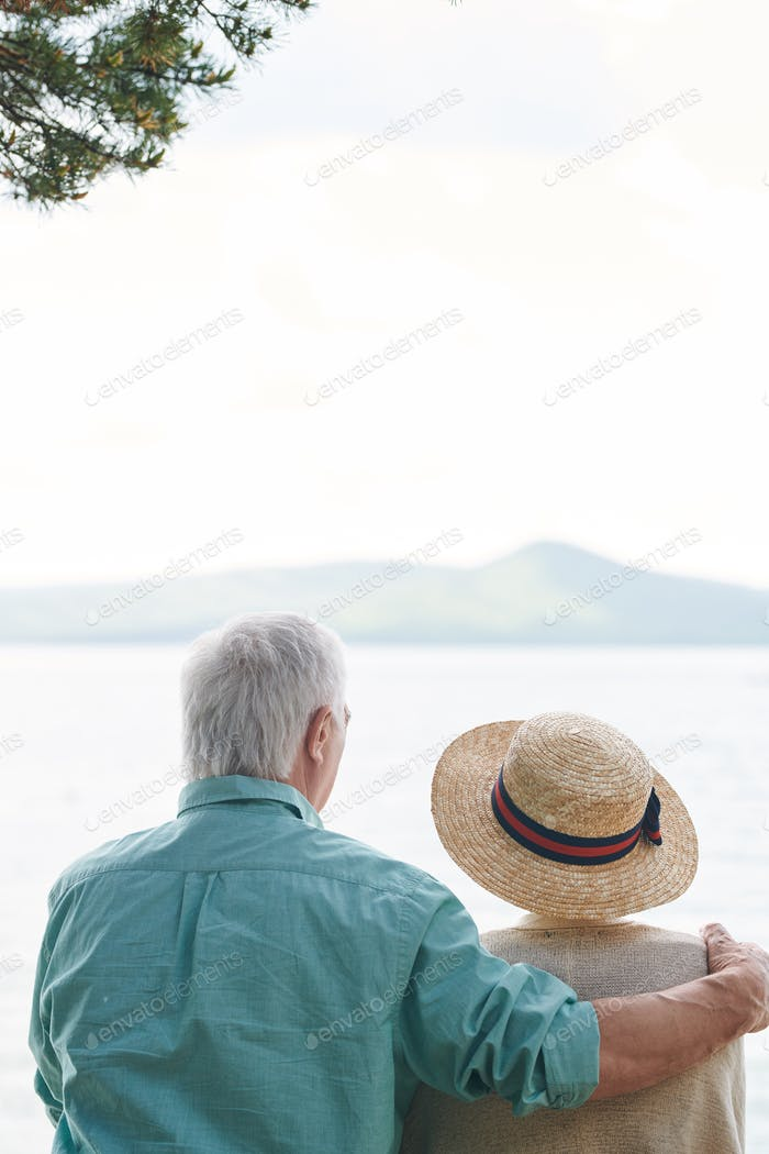 Rear view of affectionate senior spouses sitting in front of lake