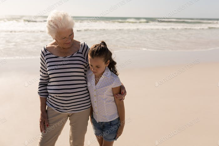 Front view of senior woman and her granddaughter with arms around standing on beach in the sunshine