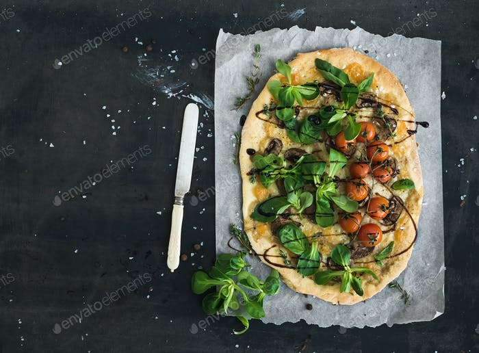 Rustic homemade pizza with fresh lamb's lettuce, mushrooms and cherry-tomatoes