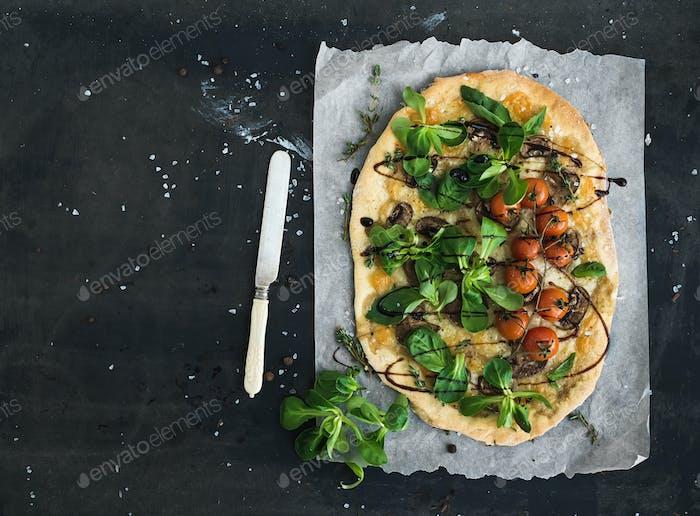 Rustikale hausgemachte Pizza mit frischem Lammsalat, Pilzen und Kirschtomaten