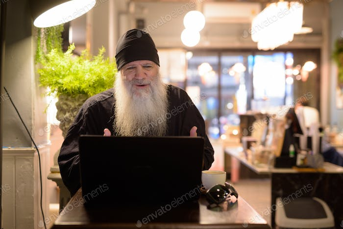 Happy mature bearded hipster man video calling with laptop at the coffee shop