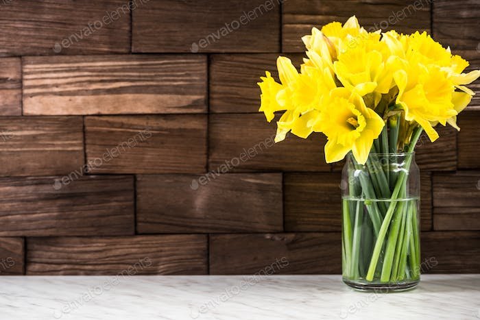 Spring yellow Daffodils flowers in vase, on wooden background