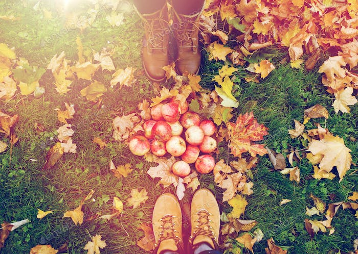 feet in boots with apples and autumn leaves