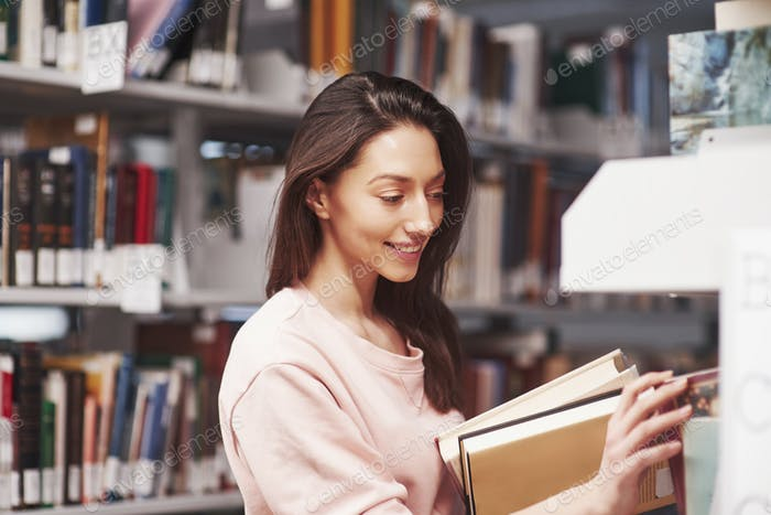 Here you are. Brunette girl in casual clothes having good time in the library full of books