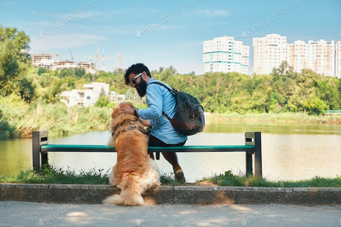 Young man sitting with his dog on the chair in the park, hugging