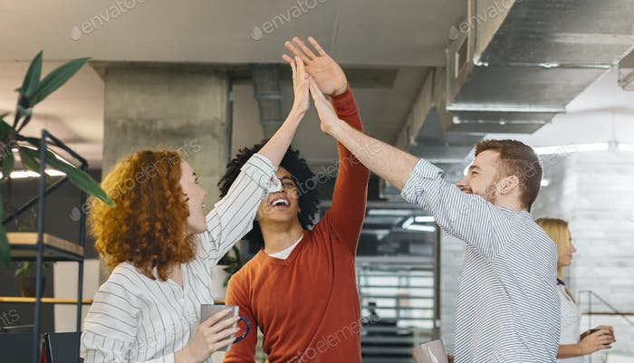 Multiracial millennial friends giving high five in office
