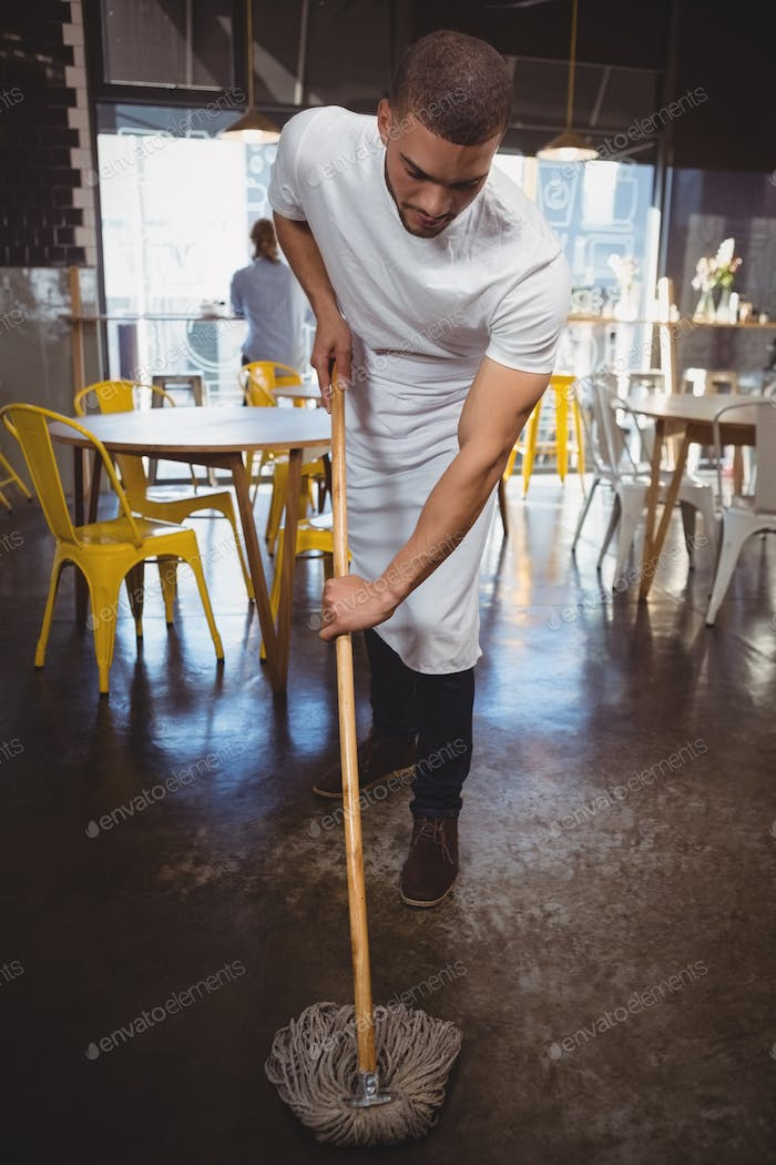 Waiter mopping floor in cafe